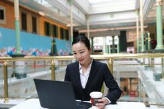 Jeune femme d'affaires s'asseyant dans le café à la table en bois, café potable Sur la table est l'ordinateur portable Image libre de droits