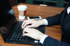 Jeune femme d'affaires s'asseyant dans le café à la table en bois, café potable Sur la table est l'ordinateur portable Images libres de droits
