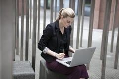Jeune femme d'affaires s'asseyant dehors avec l'ordinateur portable Image stock