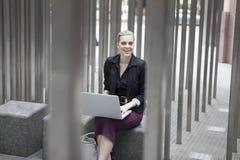 Jeune femme d'affaires s'asseyant dehors avec l'ordinateur portable Photographie stock libre de droits