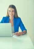 Jeune femme d'affaires s'asseyant et parlant au téléphone Photographie stock libre de droits