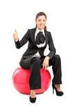 Jeune femme d'affaires s'asseyant sur la boule de pilates et renonçant au pouce Image stock