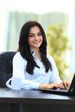 Jeune femme d'affaires s'asseyant sur le bureau Image stock