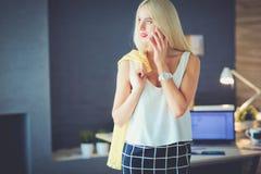 Jeune femme d'affaires s'asseyant sur le bureau avec avec la tasse Photos libres de droits