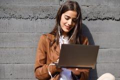 Jeune femme d'affaires s'asseyant sur le plancher regardant son compu d'ordinateur portable Images libres de droits