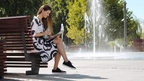 Jeune femme d'affaires s'asseyant sur une eau potable de banc et travaillant au comprimé banque de vidéos