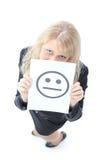 Jeune femme d'affaires se cachant derrière un visage souriant Photographie stock libre de droits
