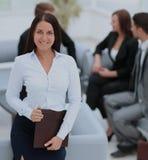 Jeune femme d'affaires se tenant avec ses collègues à l'arrière-plan a Images stock