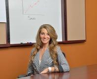 Jeune femme d'affaires se tenant devant le diagramme de ventes Photographie stock libre de droits
