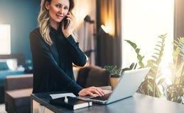 Jeune femme d'affaires se tenant d'intérieur, travaillant sur l'ordinateur, tout en parlant au téléphone portable L'entrepreneur  photographie stock
