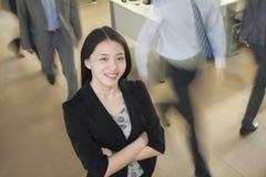 Jeune femme d'affaires souriant dans le bureau, hommes d'affaires marchant tout autour de elle Photographie stock
