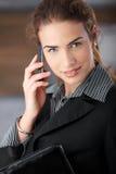 Jeune femme d'affaires souriant heureusement avec le mobile Photos libres de droits