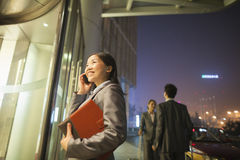 Jeune femme d'affaires souriant, marchant et parlant à son téléphone portable la nuit Photos stock