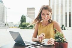 Jeune femme d'affaires sur l'ordinateur buvant d'un café Images stock