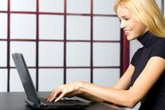 Jeune femme d'affaires sur l'ordinateur portatif photo stock