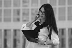 Jeune femme d'affaires sur le fond du gratte-ciel Noir et petit morceau Photos stock