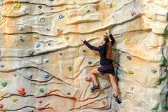 Jeune femme d'affaires sur le mur de roche Photos stock