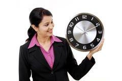 Jeune femme d'affaires tenant l'horloge dans des mains photographie stock