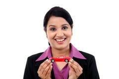 Jeune femme d'affaires tenant la voiture de jouet photo stock