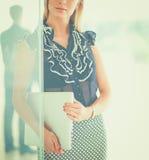 Jeune femme d'affaires tenant un ordinateur portable, se tenant sur le bureau photographie stock libre de droits