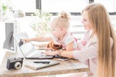 Jeune femme d'affaires travaillant à la maison derrière l'ordinateur portable avec un petit enfant Espace de travail scandinave c photos libres de droits