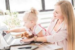 Jeune femme d'affaires travaillant à la maison derrière l'ordinateur portable avec un petit enfant Espace de travail scandinave c photographie stock