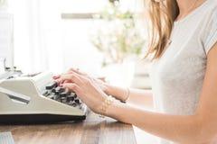 Jeune femme d'affaires travaillant à la maison et dactylographiant sur une machine à écrire Espace de travail scandinave créatif  images stock