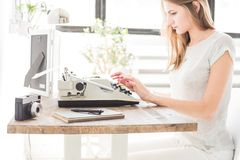 Jeune femme d'affaires travaillant à la maison et dactylographiant sur une machine à écrire Espace de travail scandinave créatif  photos stock