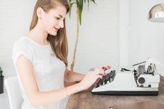 Jeune femme d'affaires travaillant à la maison et dactylographiant sur une machine à écrire Espace de travail scandinave créatif  photographie stock libre de droits