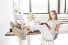 Jeune femme d'affaires travaillant à la maison et lisant un livre avec ses jambes sur la table Style scandinave créatif photographie stock libre de droits