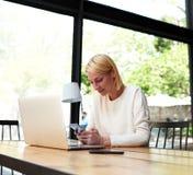 Jeune femme d'affaires travaillant au café moderne Photographie stock libre de droits