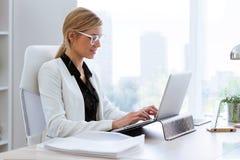 Jeune femme d'affaires travaillant avec son ordinateur portable dans le bureau Photo libre de droits