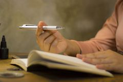 Jeune femme d'affaires travaillant avec un stylo au bureau, elle restant des heures suppl?mentaires photos libres de droits