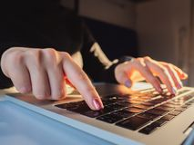 Jeune femme d'affaires travaillant sur l'ordinateur portatif Foyer sur des mains dactylographiant sur le clavier Fuites de lumièr photographie stock