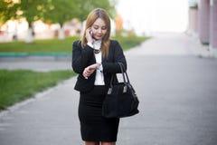 Jeune femme d'affaires vérifiant le temps sur la montre-bracelet photo libre de droits