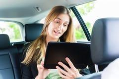 Jeune femme d'affaires voyageant dans le taxi Photographie stock