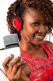 Jeune femme d'Afro-américain écoutant la musique avec des écouteurs Image stock