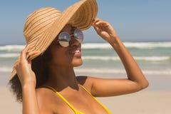 Jeune femme d'Afro-américain dans le bikini, le chapeau jaune et des lunettes de soleil se tenant sur la plage image libre de droits