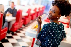 Jeune femme d'afro-américain mangeant dans le wagon-restaurant image stock