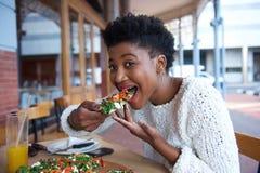 Jeune femme d'afro-américain mangeant de la pizza Image libre de droits