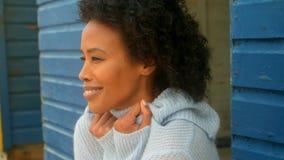 Jeune femme d'Afro-américain tremblant tout en se tenant sur la hutte de plage banque de vidéos