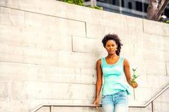 Jeune femme d'Afro-américain vous attendant avec la rose de blanc dans nouveau Images libres de droits