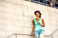Jeune femme d'Afro-américain vous attendant avec la rose de blanc dans nouveau Image libre de droits
