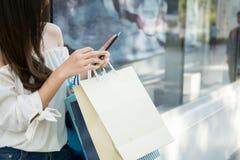 Jeune femme d'aisin à l'aide de son smartphone et panier de prise Images stock