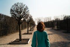 Jeune femme d'amant de mode waling en parc utilisant la veste verte vive et une jupe colorée image stock