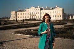Jeune femme d'amant de mode waling en parc utilisant la veste verte vive et une jupe colorée photographie stock libre de droits