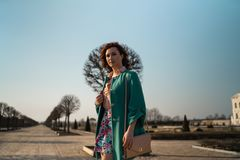 Jeune femme d'amant de mode waling en parc utilisant la veste verte vive et une jupe colorée image libre de droits
