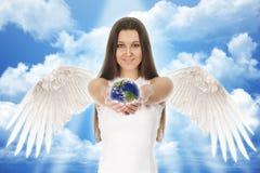 Jeune femme d'ange tenant la terre dans des mains avec des nuages photos stock