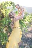 Jeune femme d'Eautiful avec une fille d'enfant dans le domaine des raisins Photos stock