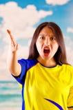 Jeune femme d'ecuadorian portant l'appareil-photo debout de revêtement de marathon de chemise officielle du football, langage du  Photos stock